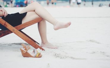 Pair of legs visible from deck chair on beach