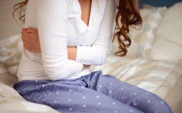 Woman in pyjamas sat on bed clutching stomach