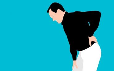 Cartoon of man bending over in back pain
