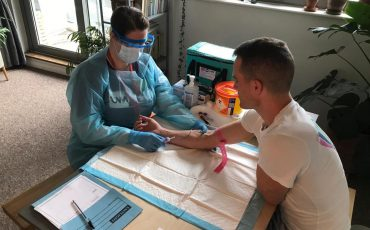 Nurse in PPE draws blood from man