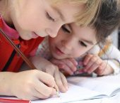 two small children writing in a book