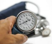 person holding blood pressure monitor