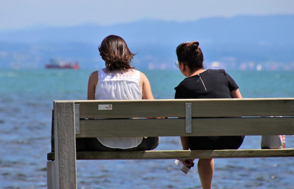 Two women sitting on a bench looking at the ocean