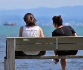 two women sitting on bench facing ocean